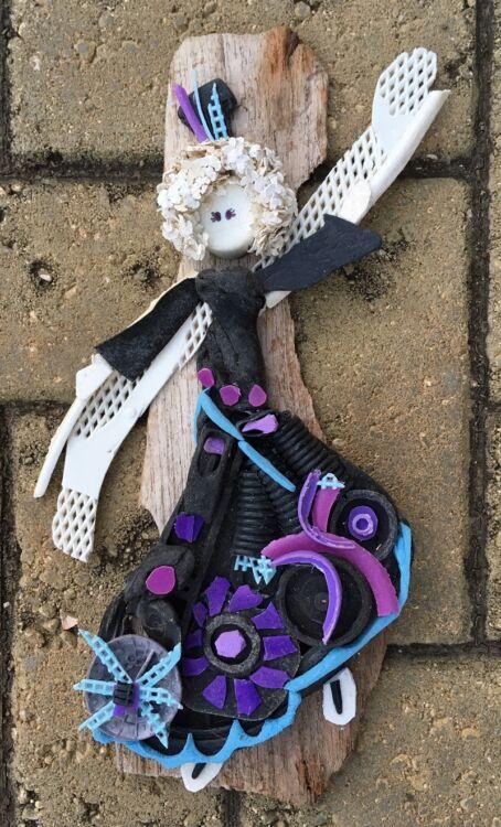 Beschermengel van zeeplastic op drijfhout in kleueren zwart, baby blauw en paars